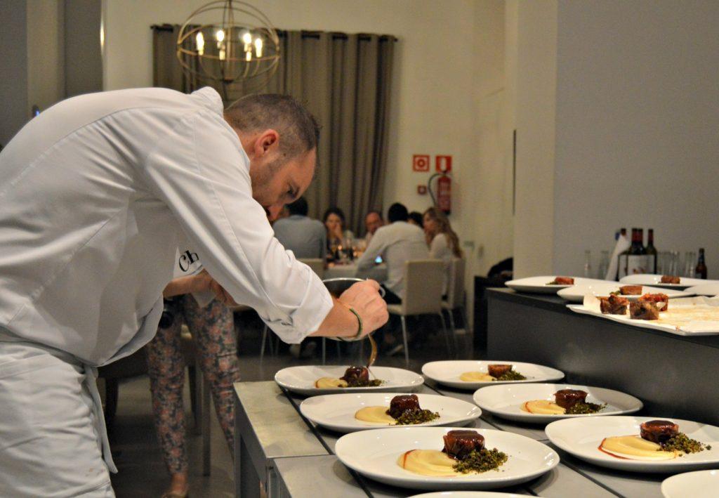 El chef Tomeu Martí, rematando un plato con los comensales del Hidden Kitchen al fondo