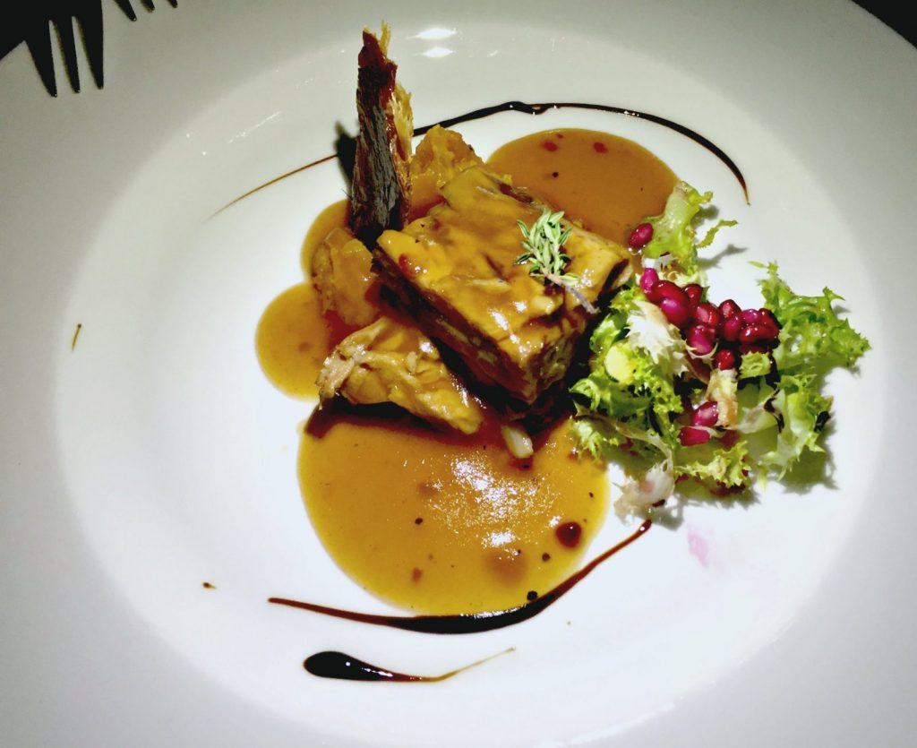 Lechoncita de cerdo negro con salsa de granada, boniato rojo y escarola